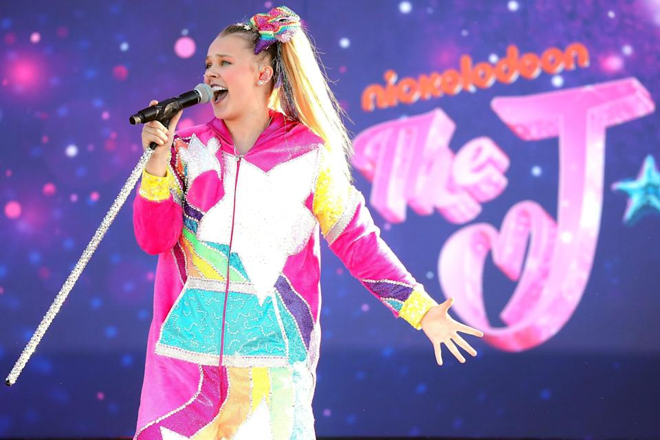 JoJo Siwa performing in a brightly colored outfit