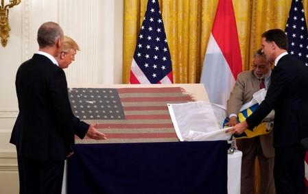 Trump and Netherlands Prime Minister Rutte take part in a flag presentation at the White House in Washington