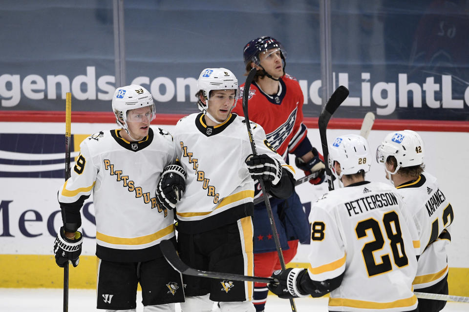 Pittsburgh Penguins left wing Jake Guentzel (59) celebrates his goal with defenseman John Marino (6), defenseman Marcus Pettersson (28) and right wing Kasperi Kapanen (42) during the second period of an NHL hockey game as Washington Capitals left wing Carl Hagelin skates by at back, Tuesday, Feb. 23, 2021, in Washington. (AP Photo/Nick Wass)