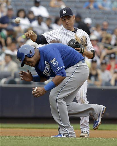 New York Yankees' Luis Cruz, top, throws to first over Kansas City Royals' Salvador Perez during the first inning of the baseball game at Yankee Stadium Thursday, July 11, 2013 in New York. (AP Photo/Seth Wenig)