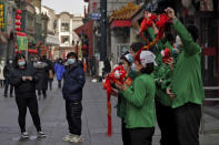 "A man and a woman, both wearing face masks to help curb the spread of the coronavirus, look at workers holding lunar new year deco and ox soft toys cheer outside their retail shop near Qianmen Street, a popular tourist spot in Beijing, Sunday, Jan. 31, 2021. China and WHO expert team will carry out ""scientific and rigorous joint research"" on looking into the COVID-19 origins, the National Health Commission said on Sunday. (AP Photo/Andy Wong)"