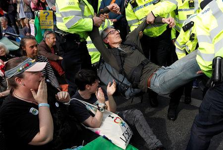 Police officers detain a climate change activist at Waterloo Bridge during the Extinction Rebellion protest in London, Britain April 18, 2019. REUTERS/Peter Nicholls