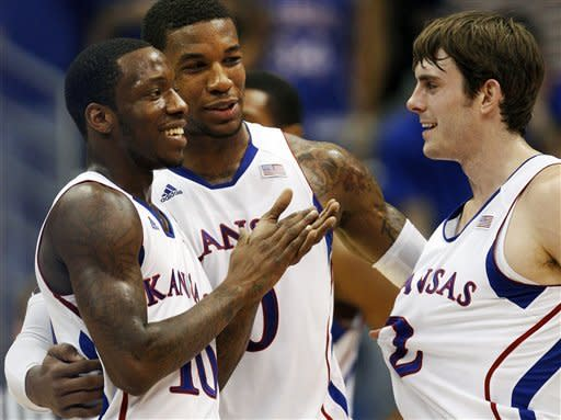 Kansas forward Thomas Robinson, center, talks with teammates Tyshawn Taylor, left, and Conner Teahan (2) during a timeout in the first half of an NCAA college basketball game against Texas Tech in Lawrence, Kan., Saturday, Feb. 18, 2012. (AP Photo/Orlin Wagner)
