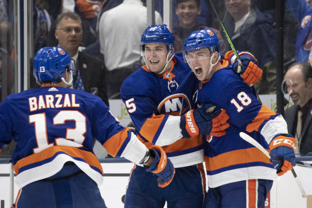 New York Islanders left wing Anthony Beauvillier (18) celebrates his game-winning overtime goal against the Buffalo Sabres with teammates Mathew Barzal (13) and Devon Toews, center, in an NHL hockey game, Saturday, Dec. 14, 2019 in Uniondale, N.Y. The Islanders won 3-2. (AP Photo/Mark Lennihan)