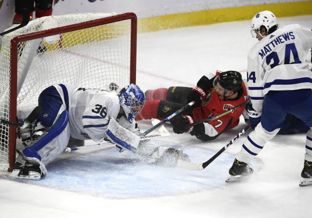 Toronto Maple Leafs goaltender Jack Campbell (36) puts his glove on the puck as Ottawa Senators left wing Brady Tkachuk (7) tries to get his stick on it and Leafs' center Auston Matthews (34) defends during third-period NHL hockey game action in Ottawa, Ontario, Saturday, Feb. 15, 2020. (Justin Tang/The Canadian Press via AP)