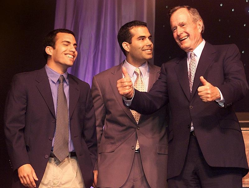 "John ""Jebby"" Bush, and brother George P. Bush watch their grandfather, former President George H. W. Bush, give a ""thumbs up"" sign at Governor Jeb Bush's Inauguration Party."