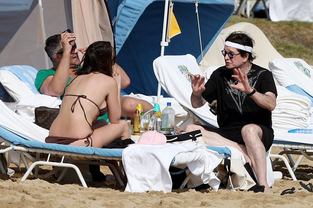 """What, you expected """"Prince of Darkness"""" Ozzy Osbourne to wear a color other than black to the beach? Still, you can tell the rock legend and former reality TV star doesn't take himself too seriously thanks to the smiley face scribbled on his knee. <a href=""""http://www. PacificCoastNews.com"""" target=""""new"""">PacificCoastNews.com</a> - January 4, 2010"""