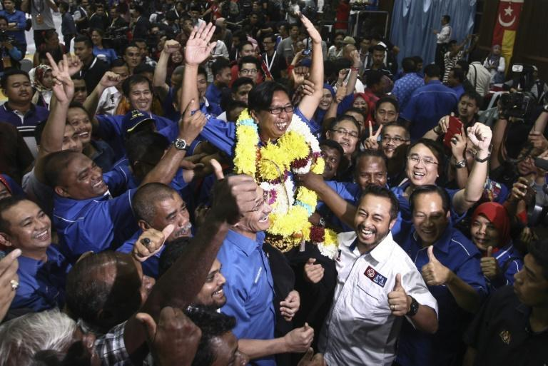 Supporters of the United Malays National Organisation (UMNO) hoist Budiman Mohamad Zohdi after he won a by-election in Sungai Besar, a coastal town outside Kuala Lumpur on June 18, 2016