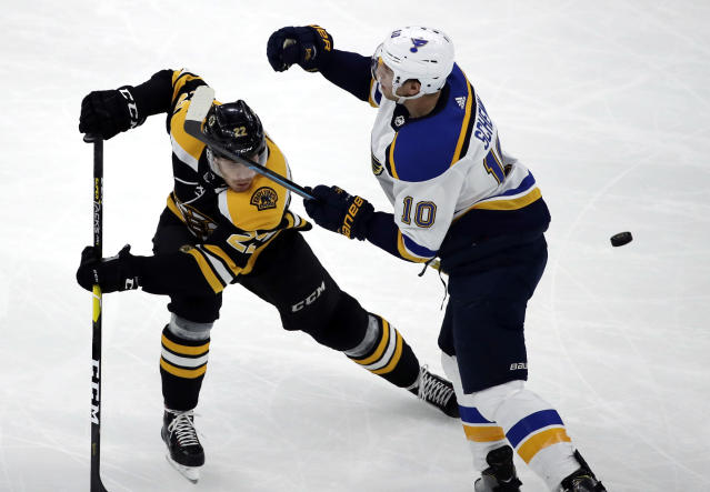 Boston Bruins left wing Peter Cehlarik (22) and St. Louis Blues center Brayden Schenn (10) compete for the puck during the first period of an NHL hockey game Thursday, Jan. 17, 2019, in Boston. (AP Photo/Elise Amendola)