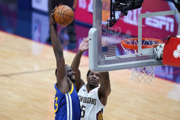 Golden State Warriors forward Draymond Green slam dunks against New Orleans Pelicans guard Eric Bledsoe (5) in the first half of an NBA basketball game in New Orleans, Monday, May 3, 2021. (AP Photo/Gerald Herbert)