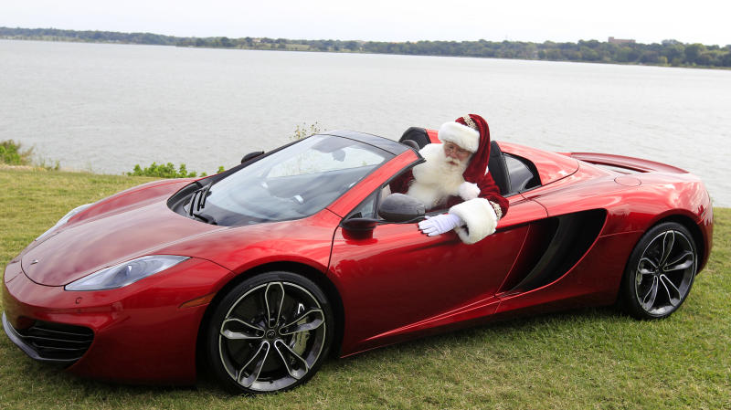 Brady White portrays Santa Clause as he shows off a 2013 McLaren 12C spider sports car during the unveiling of the Neiman Marcus 2012 Christmas Book in Dallas, Tuesday, Oct. 9, 2012.  The Neiman Marcus edition is one of 12 made and priced at $354,000. (AP Photo/LM Otero)