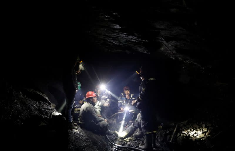 Artisanal gold miners talk as they sit inside a gold mine in La Rinconada, in the Andes