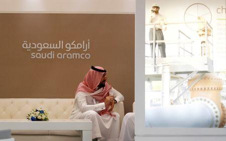FILE PHOTO:A Saudi Aramco employee sits in the area of its stand at the Middle East Petrotech 2016 in Manama