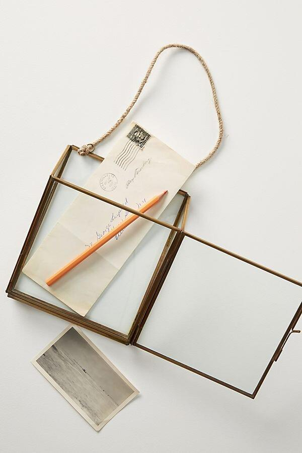 """<p>Part storage, part wall art, this hanging glass and brass pocket is the perfect organizer for your front entryway. </p> <p><strong>To buy: </strong>$38, <a href=""""https://click.linksynergy.com/deeplink?id=93xLBvPhAeE&mid=39789&murl=https%3A%2F%2Fwww.anthropologie.com%2Fshop%2Fhanging-pocket-frame2&u1=RS%2CAnthropologieJustLaunchedMoreThan1%252C700NewHomeItems%25E2%2580%2594Our5FavoritesUnder%252450%2Ckholdefehr1271%2CDEC%2CIMA%2C691325%2C202001%2CI"""" target=""""_blank"""">anthropologie.com</a>. </p>"""