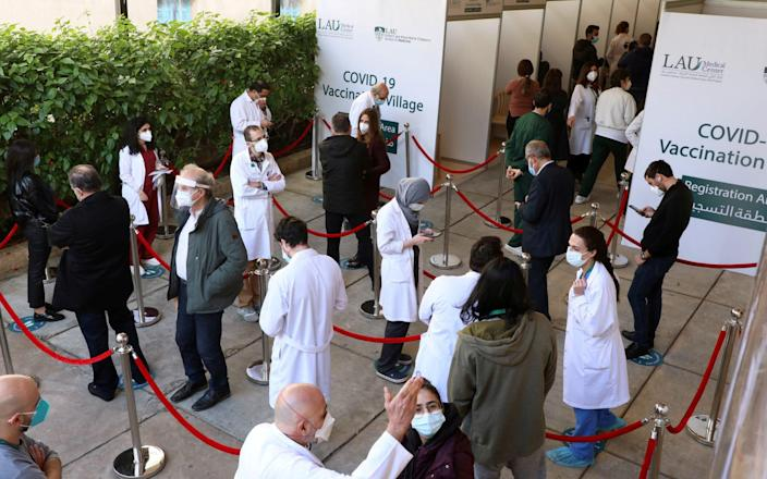 Health workers wait to receive the Pfizer/BioNTech Covid-19 vaccine in Beirut - Reuters