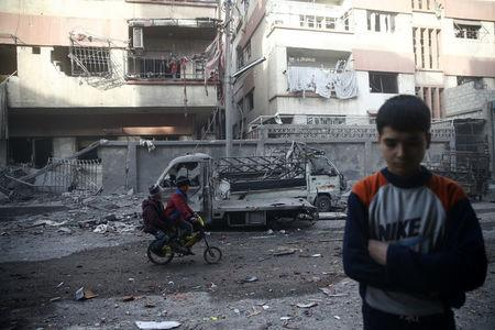 Children ride on a bicycle at a damaged site after an airstrike in the besieged town of Douma, Eastern Ghouta, Damascus, Syria February 9, 2018. REUTERS/Bassam Khabieh