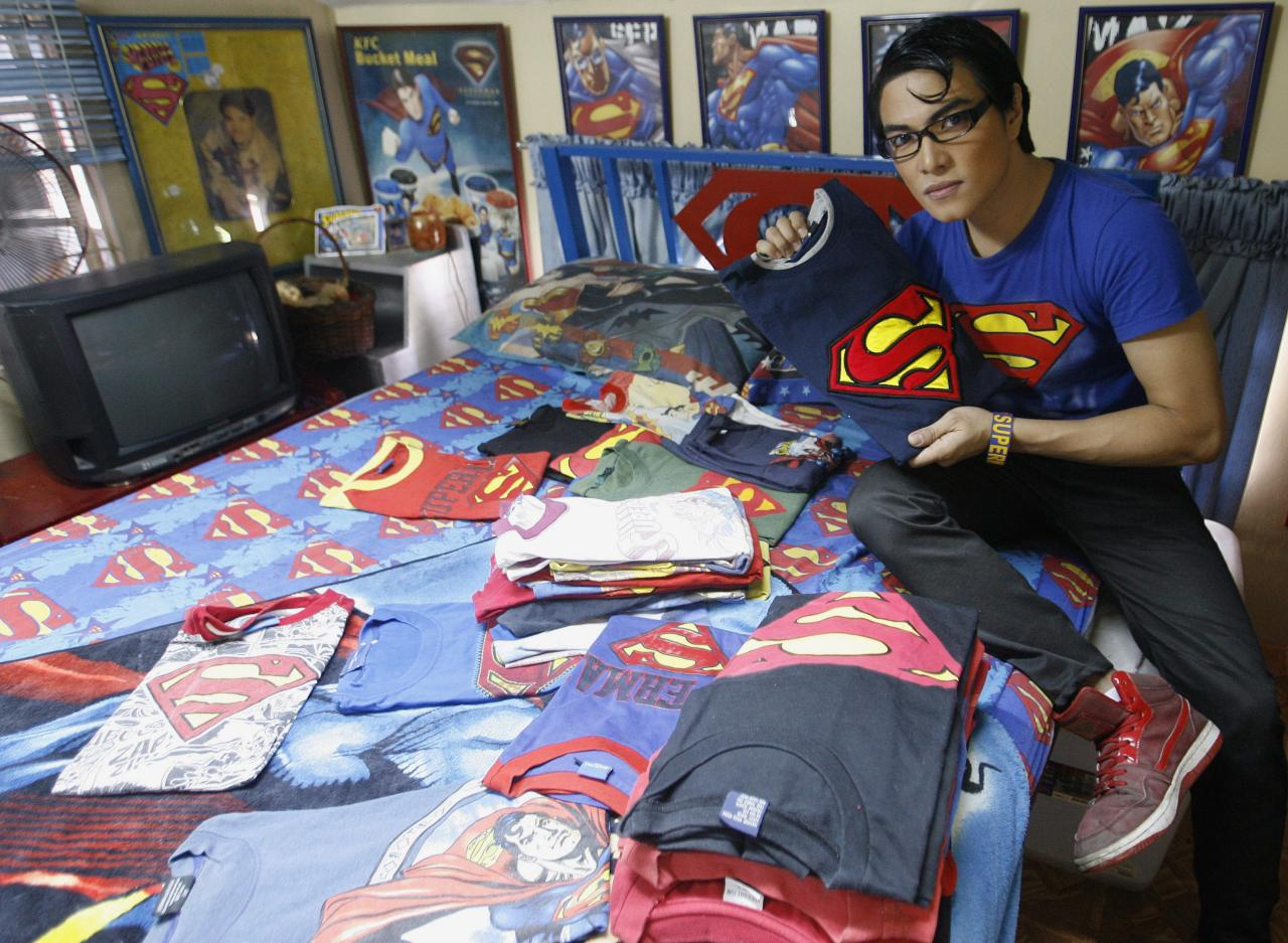 "Herbert Chavez shows off his Superman shirt collection, some of which were made by him, inside his bedroom in Calamba Laguna, south of Manila October 12, 2011. In his idolization of the superhero, Chavez, a self-professed ""pageant trainer"" who owns two costume stores, has undergone a series of cosmetic surgeries for his nose, cheeks, lips and chin down to his thighs and even his skin color to look more like the ""Man of Steel"". The final result bears little resemblance to his old self. REUTERS/Cheryl Ravelo (PHILIPPINES - Tags: SOCIETY)"