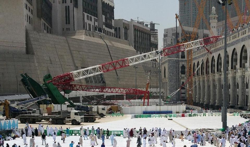 Pilgrims walk past the crane that collapsed on September 11, 2015 at the Grand Mosque in Mecca (AFP Photo/-)