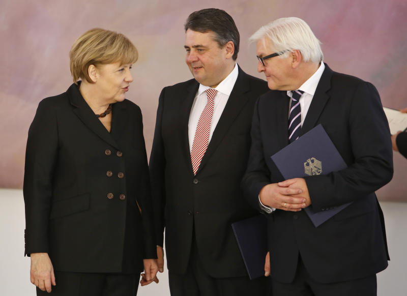 German Chancellor Angela Merkel talks to German Economy and Energy Minister Sigmar Gabriel and German Foreign Minister Frank-Walter Steinmeier, from left, after the ministers were appointed in Berlin Tuesday, Dec. 17, 2013. (AP Photo/Ferdinand Ostrop)
