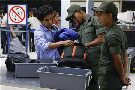 Soldiers checks the luggage of a passenger in a security checkpoint at the Simon Bolivar airport in La Guaira outside Caracas October 15, 2013. REUTERS/Carlos Garcia Rawlins