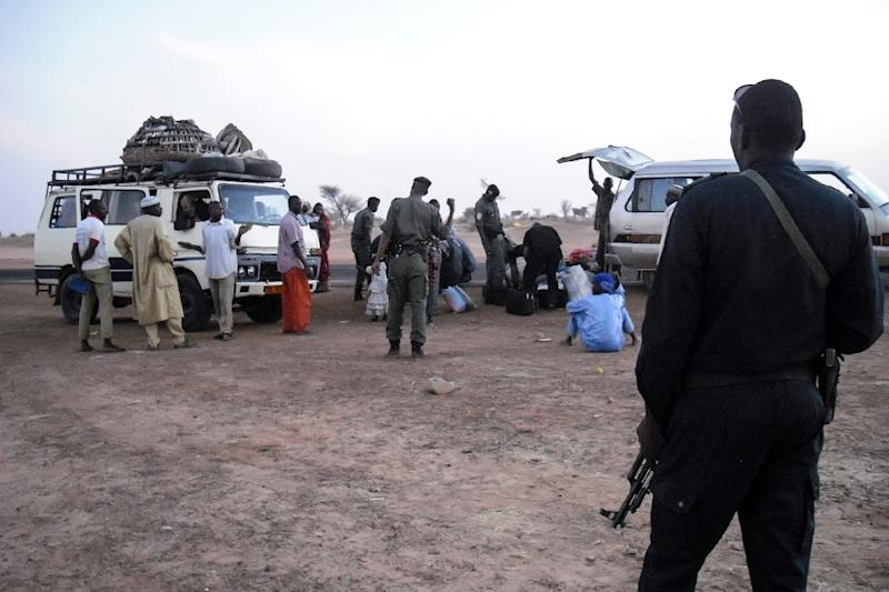Buses full of displaced people from the Diffa region of Niger fleeing fighting between army and Boko Haram on the border between Niger and Nigeria are checked by police on the outskirts of Zinder pictured on February 13, 2014 (AFP Photo/Robert Leslie)