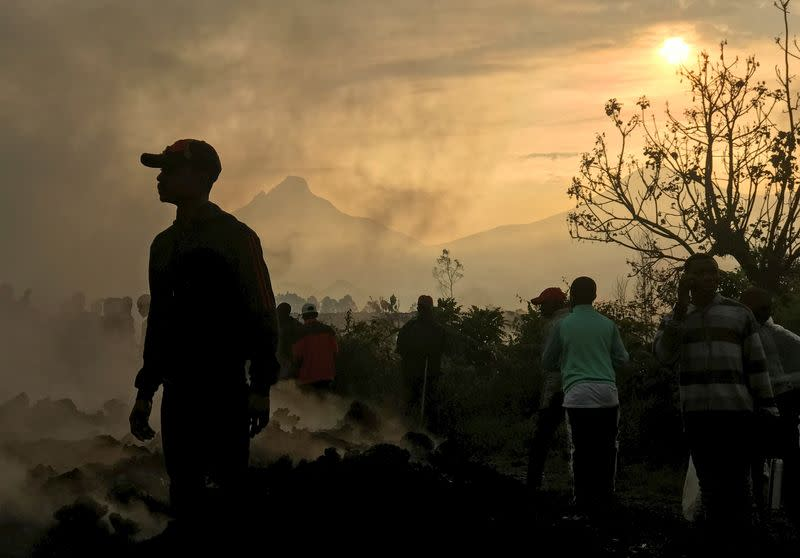 Residents walk near destroyed homes with the smouldering lava deposited by the eruption of Mount Nyiragongo volcano near Goma