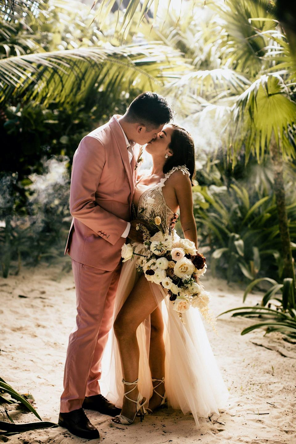 The Baks kiss in front of trees in their wedding attire