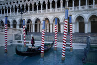 A gondolier stands by a boat near a quiet pedestrian walkway at the Venetian hotel and casino in Las Vegas, Feb. 4, 2021. The toll of the coronavirus is reshaping Las Vegas almost a year after the pandemic took hold. The tourist destination known for bright lights, big crowds, indulgent meals and headline shows is a much quieter place these days. (AP Photo/John Locher)