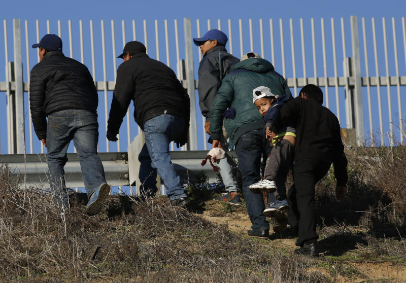 FILE - In this Dec. 12, 2018 file photo, Honduran migrants, one carrying a child, who plan to turn themselves over to U.S. border patrol agents, walk up the embankment after climbing over the U.S. border wall from Playas de Tijuana, Mexico in Tijuana, Mexico. The group crossed to apply for asylum. A federal judge on Friday, May 17, 2019, in California will consider a challenge to President Donald Trump's plan to tap billions of dollars from the Defense and Treasury departments to build his prized border wall with Mexico. (AP Photo/Moises Castillo, File)