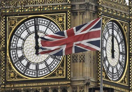 A British Union Jack flag is seen flying near a face of the clocktower at the Houses of Parliament in London, Britain