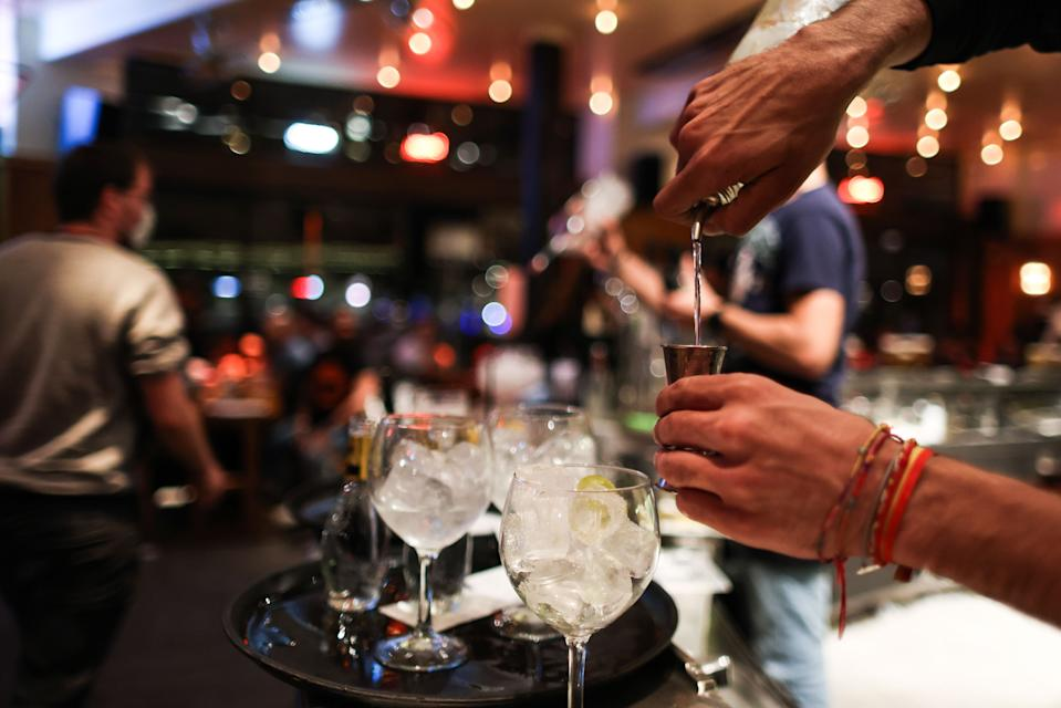 A waiter serves a cocktail at a bar on the eve of the mandatory closure of bars in Brussels, on October 7, 2020, to stop the spread of Covid-19. - In Brussels, bars and drinking alcohol in public places will be banned until November 8, the regional government said. An 11pm bar curfew had already been announced for the rest of the country. (Photo by Kenzo TRIBOUILLARD / AFP) (Photo by KENZO TRIBOUILLARD/AFP via Getty Images)