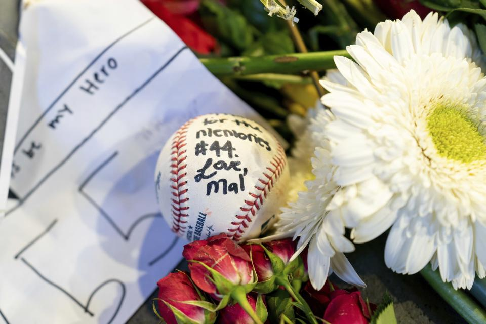 "Memorabilia left behind by fans is shown during ""A Celebration of Henry Louis Aaron,"" a memorial service celebrating the life and enduring legacy of the late Hall of Famer and American icon, on Tuesday, Jan. 26, 2021, at Truist Park in Atlanta. (Kevin D. Liles/Atlanta Braves via AP, Pool)"