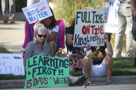 Staci Patrick, left, protests with others in front of the Davis School District Office, Tuesday, Aug. 4, 2020, in Farmington, Utah. A group of parents protested the district's hybrid reopening plan because they would prefer their children to attend school five days a week. (AP Photo/Rick Bowmer)