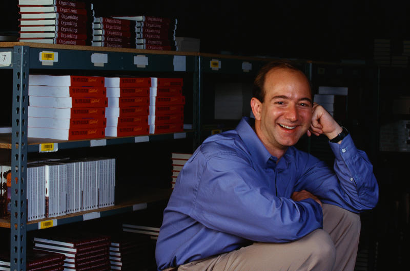 Amazon.com's CEO Jeff Bezos Next to Bookshelves