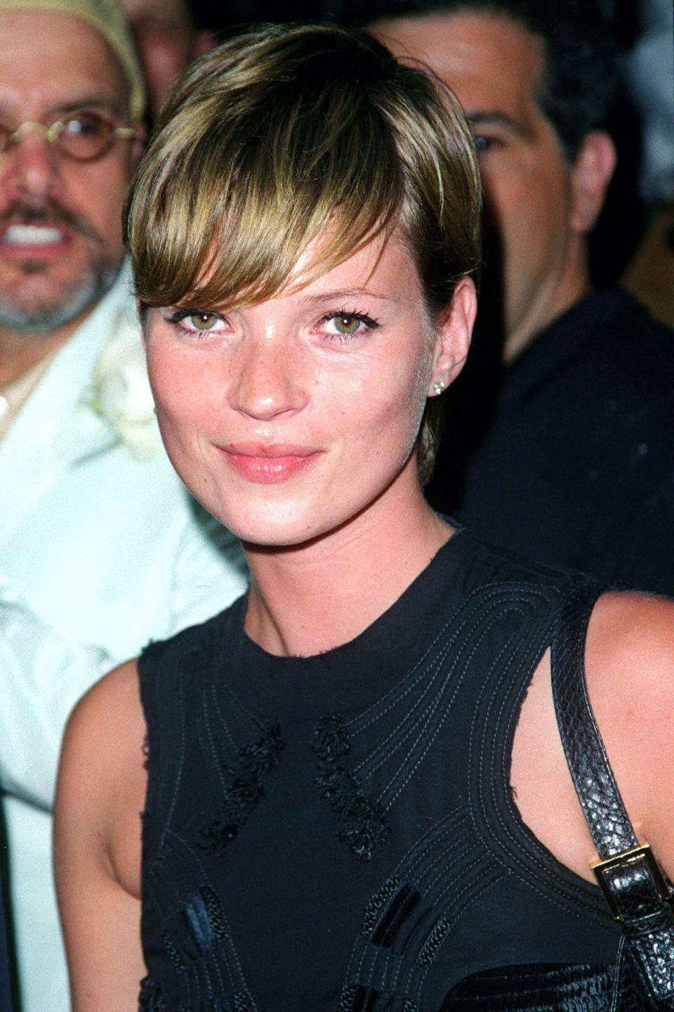 <p>Model Kate Moss plays with feathery fringe bangs.</p>