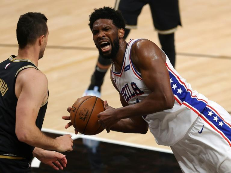 Philadelphia 76ers' Joel Embiid, right, reacts as he falls to the floor prior to being charged with an offensive foul while driving into Clint Capela of the Atlanta Hawks