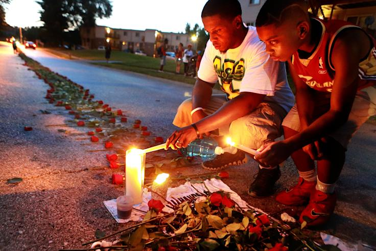 Theo Murphy, left, and his brother Jordan Marshall, 11, light candles at a memorial where unarmed Michael Brown was fatally shot by Ferguson Police Officer Darren Wilson. (AP/Post-Dispatch, Christian Gooden)