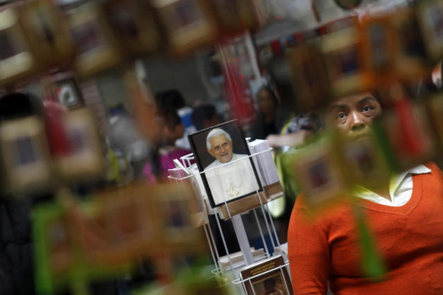 A woman looks at religious articles at a shop in the Basilica of Guadalupe in Mexico City February 11, 2013. Pope Benedict stunned the Roman Catholic Church including his closest advisers on Monday when he announced he would stand down in the first papal abdication in 700 years, saying he no longer had the mental and physical strength to run the Church through a period of major crisis. REUTERS/Edgard Garrido (MEXICO - Tags: RELIGION) - RTR3DNM0