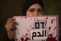 """Protesters hold signs and chant slogans during a demonstration against violence near the house of Public Security Minister Omer Barlev in the central Israeli town of Kokhav Ya'ir, Saturday, Sept. 25, 2021. Arab citizens of Israel are seeking to raise awareness about the spiraling rate of violent crime in their communities under the hashtag """"Arab lives matter,"""" but unlike a similar campaign in the United States, they are calling for more policing, not less. Sign reads: """"Blood""""(AP Photo/Sebastian Scheiner)"""