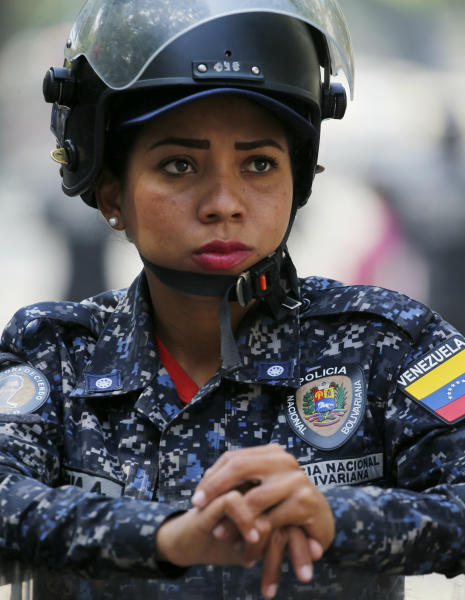 A police stands guard in anticipation of a march called by a coalition of opposition parties and civic groups who are petitioning lawmakers for a law of guarantees that will protect workers who have been victims of political retaliation and unjustified dismissals, in Caracas, Venezuela, Tuesday, March 19, 2019. (AP Photo/Fernando Llano)
