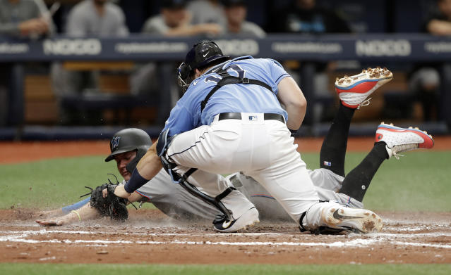 Tampa Bay Rays catcher Mike Zunino (10) tags out Miami Marlins' Miguel Rojas who was attempting to steal home plate during the sixth inning of a baseball game Sunday, Aug. 4, 2019, in St. Petersburg, Fla. (AP Photo/Chris O'Meara)