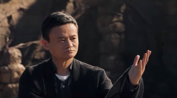 Alibaba founder Jack Ma looks pensive while raising his left hand.