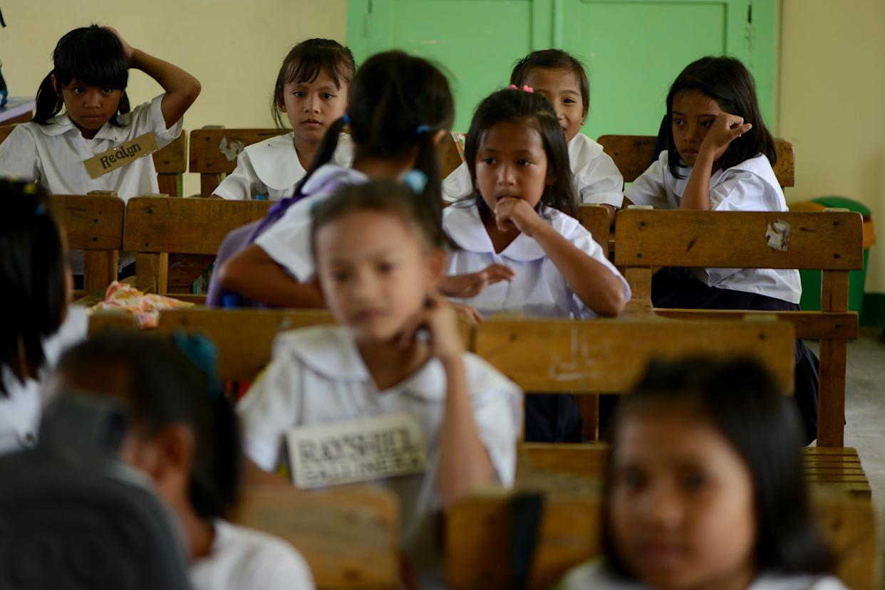 Genesis Tuazon (top right), 8, sits inside a classroom at the Panghulo Elementary School near the Artex Compound in Malabon City on June 5, 2013.