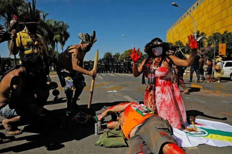 Indigenous Brazilian people act out a performance in front of riot police during a protest outside Congress in Brasilia, on June 22, 2021