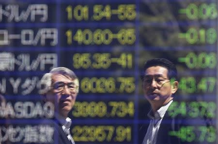 Tokyo businessmen are reflected in an electronic board showing exchange rates between the Japanese yen against foreign currencies and markets indices, outside a brokerage in Tokyo