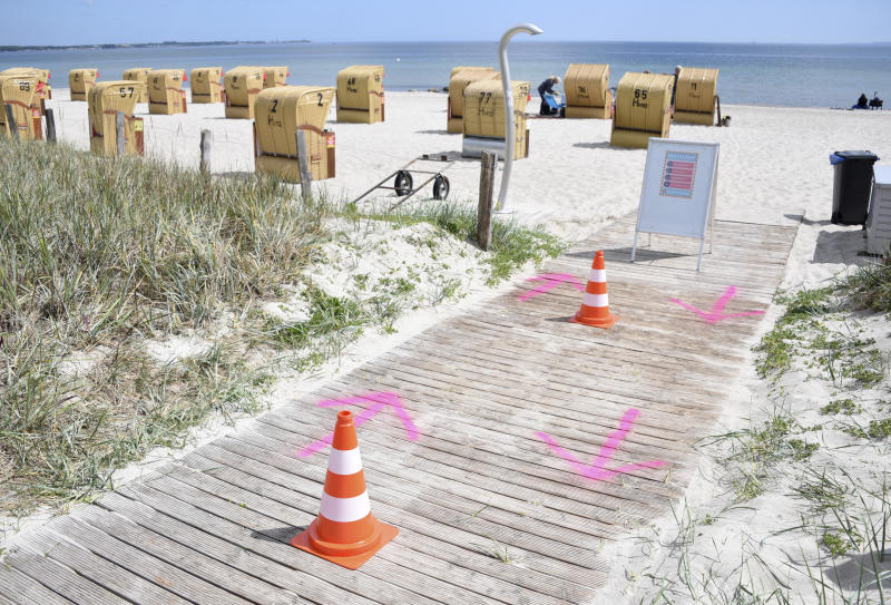 In this Wednesday, May 20, 2020 photo, pylons and arrows sprayed on the ground, regulate the access to the beach at the Baltic Sea in Haffkrug, Germany. Germany's states, which determine their own coronavirus-related restrictions, have begun loosening lockdown rules to allow domestic tourists to return. (Daniel Bockwoldt/dpa via AP)