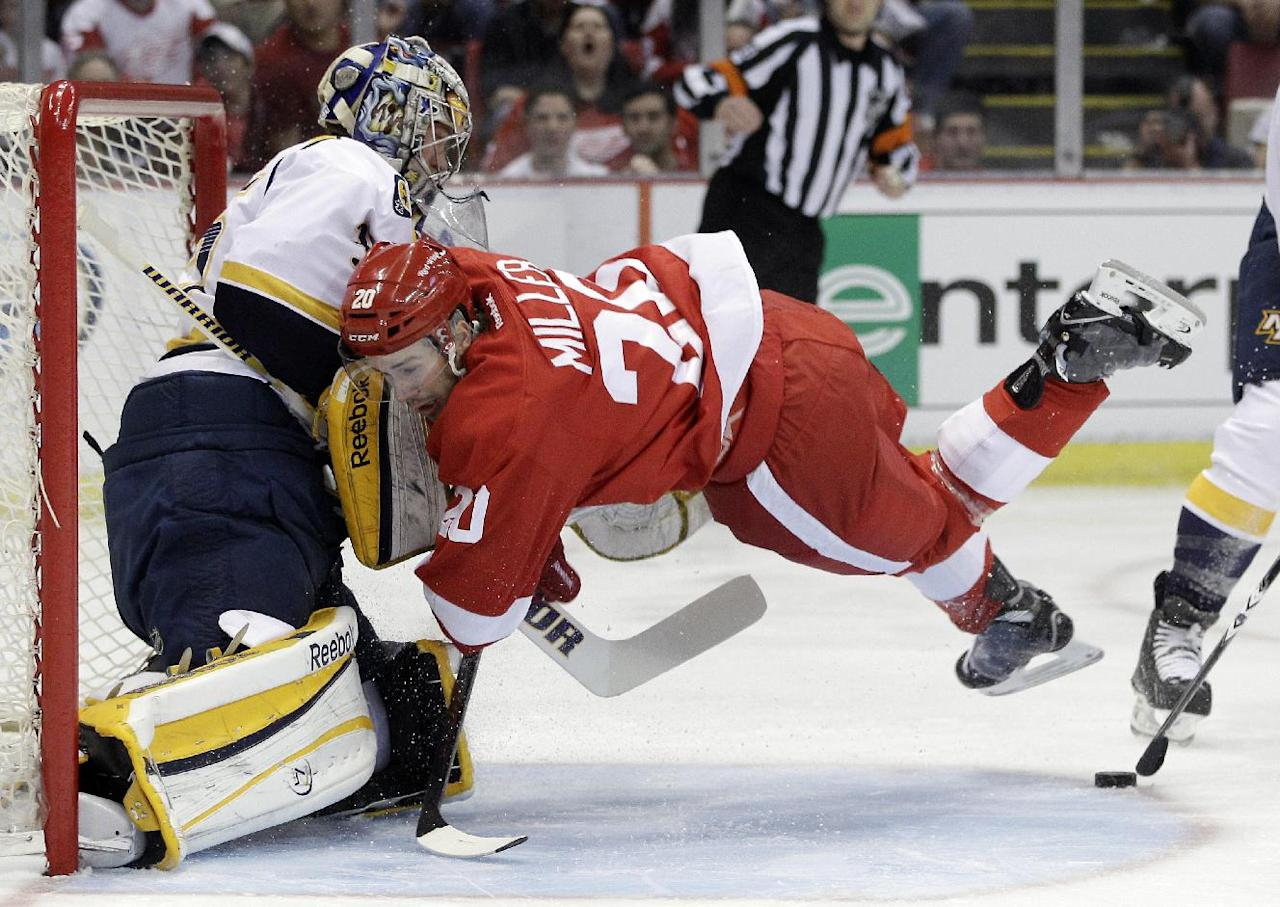 Detroit Red Wings left wing Drew Miller (20) runs into Nashville Predators goalie Pekka Rinne, left, of Finland, during the first period of Game 3 of an NHL hockey Stanley Cup first-round playoff series in Detroit, Sunday, April 15, 2012. (AP Photo/Carlos Osorio)