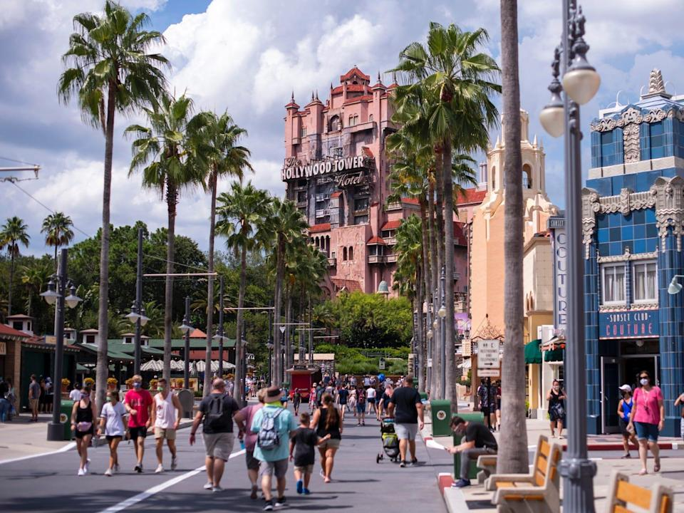 This image shows palm trees and colorful buildings among walking crowds at Disney World.