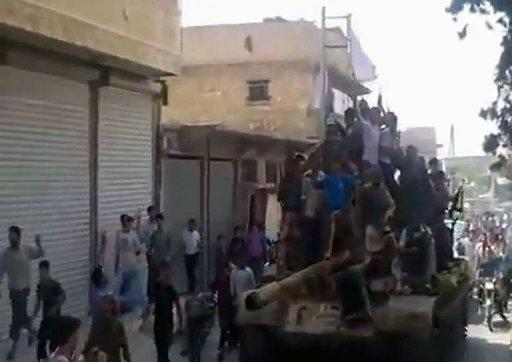 A YouTube video shows crowds greeting Syrian rebels as they parade through a street atop a tank in Al-Bab in the northern province of Aleppo on July 29, 2012. AFP is using pictures from alternative sources. Around 200,000 civilians have fled fighting in Syria's most populous city Aleppo and many more were trapped, the UN said as a fierce government offensive against rebels entered a second day