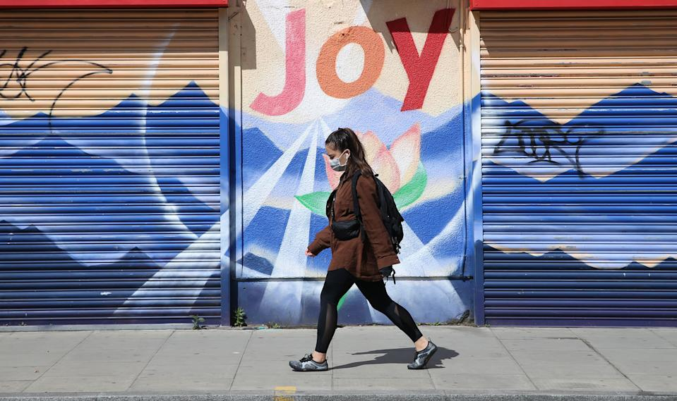 """A woman wearing a face mask walks past a graffiti that reads """"Joy"""" in Dalston, Hackney, east London, as the UK continues in lockdown to help curb the spread of the coronavirus. Picture date: Saturday May 2, 2020."""